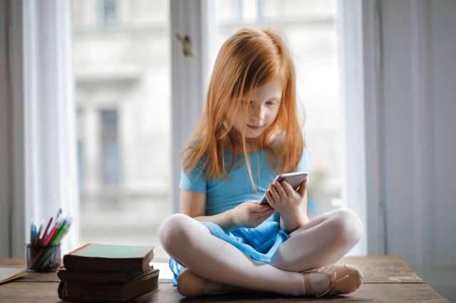 Menina sentada usando celular
