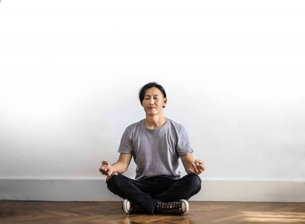 Homem sentado em posição de meditação.
