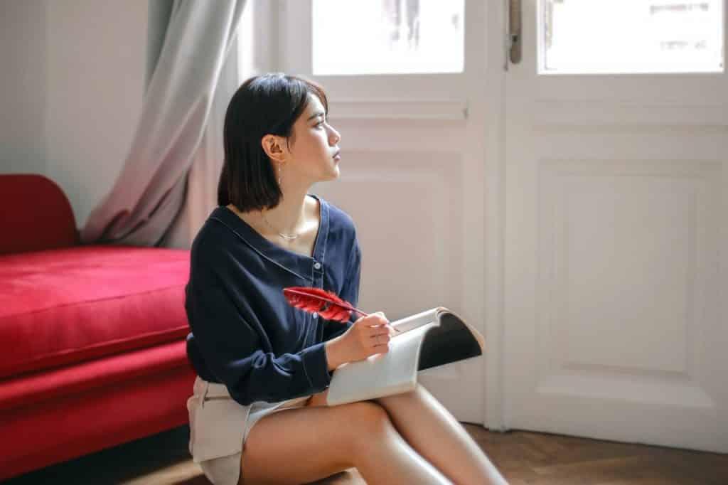 Mulher sentada no chão escrevendo em seu caderno enquanto olha para o lado.