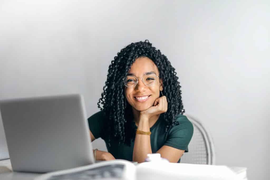 Mulher negra sorrindo com a cabeça apoiada na mão.