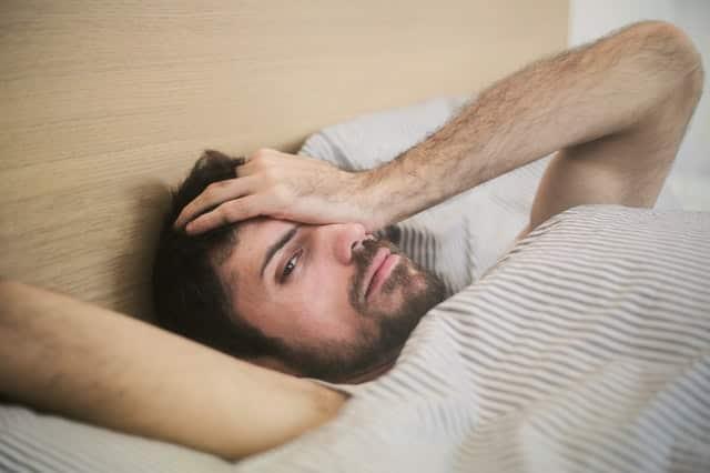 Homem deitado na cama com mão no rosto e expressão de preguiça