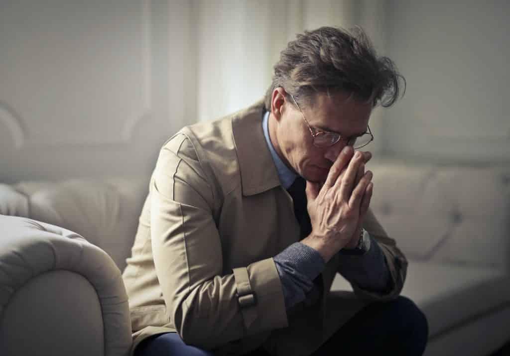 Homem sentado no sofá, com expressão séria e as mãos sobre o rosto.