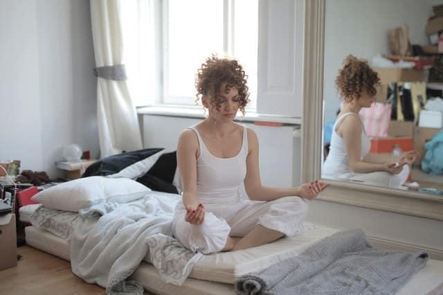 Mulher meditando em posição de lótus em colchão no chão no quarto