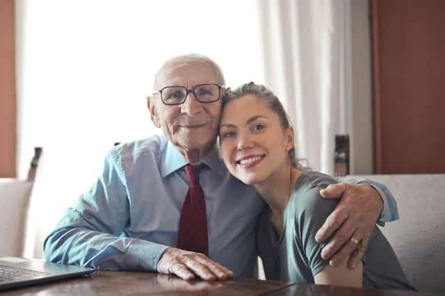 Avô abraçando neta jovem e ambos sorrindo