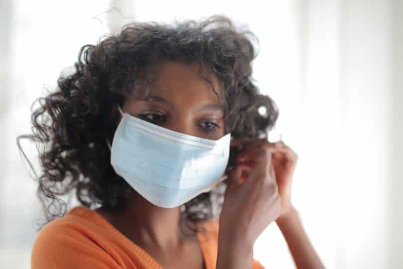 Mulher colocando máscara de proteção