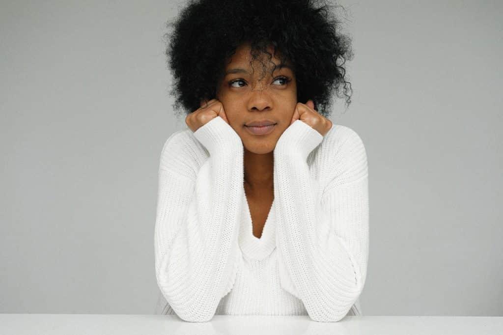 Mulher de cabelos cacheados sentada, segurando a cabeça com as mãos.
