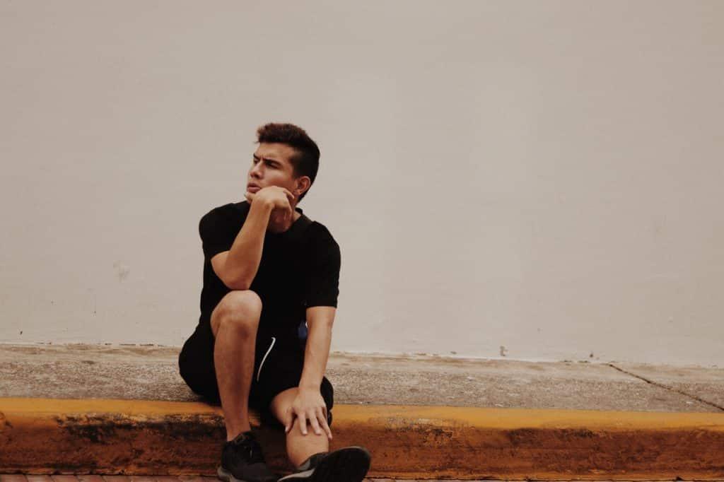 Homem sentado em uma calçada apoiando sua mão no rosto