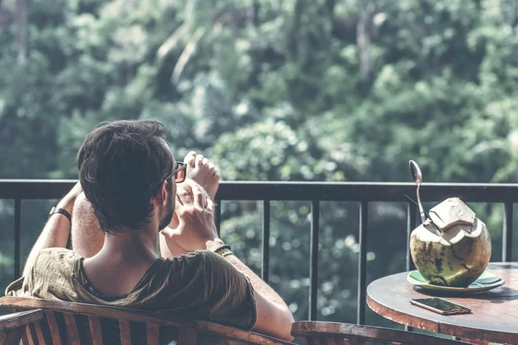 Homem sentado com as pernas para cima, ao lado de um coco com um canudo.