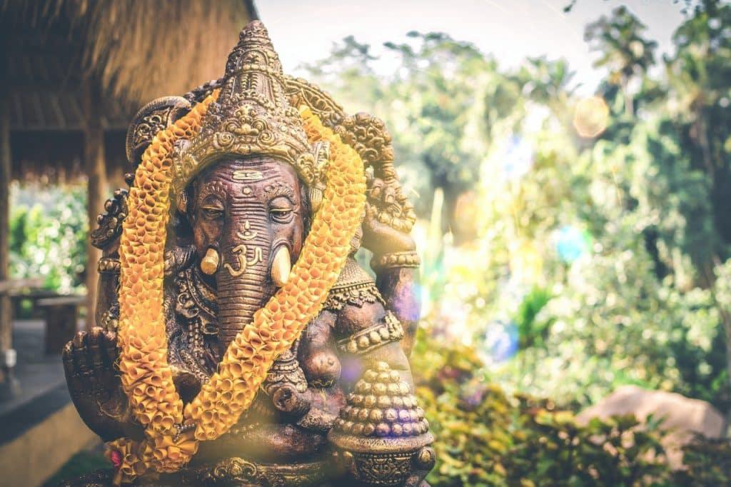 Estátua de Lord Ganesha em bronze com um colar de flores laranjas em seu pescoço. Ganesha é um deus com corpo de homem, com quatro braços e a cabeça de elefante. Ao fundo há algumas árvores.