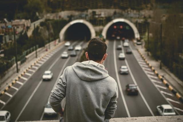 Homem em pé de costas em ponte com carros passando lá embaixo