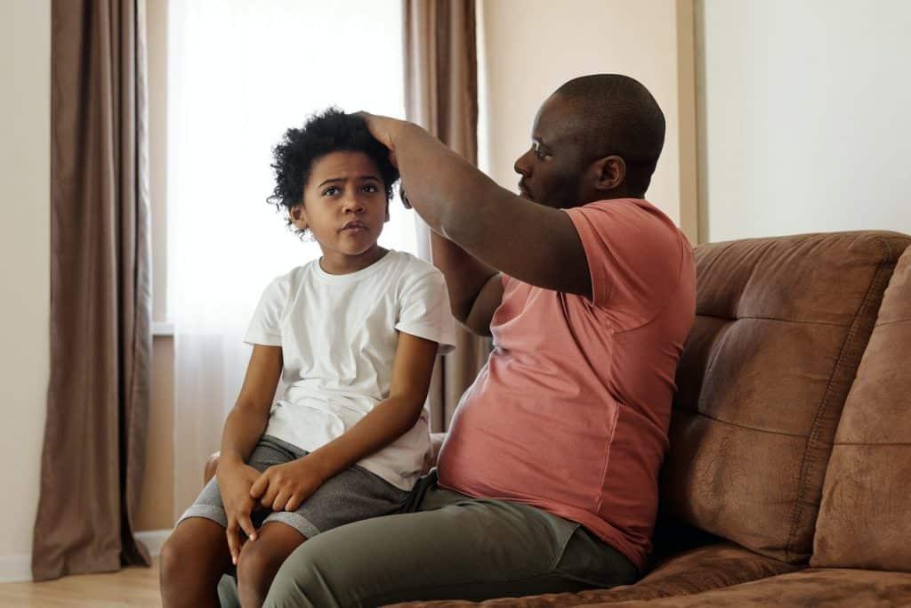 Pai arrumando o cabelo do filho enquanto ambos conversam no sofá.