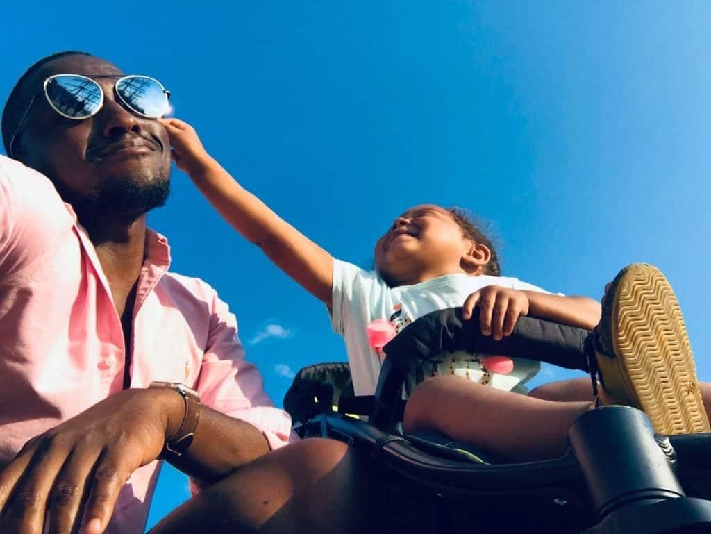 Pai e filha negros, a filha com mão levantada encostando na bochecha do pai.