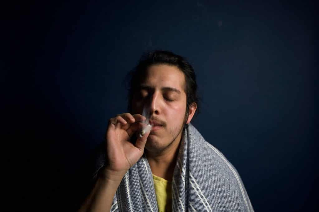 Homem branco de bigode fumando maconha.