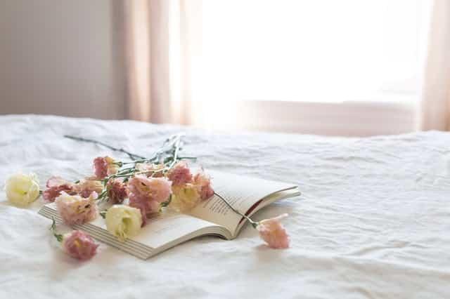 Livro aberto numa cama com flores roxas e amarelas em cima