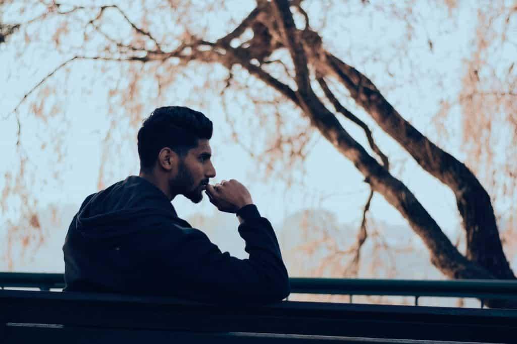 Homem sentado em um banco, com a mão no queixo, pensando.