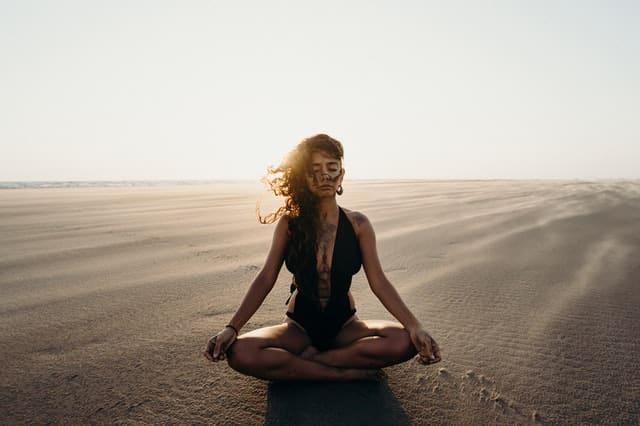 Mulher sentada em posição se lótus em deserto de olhos fechados e sol refletindo ao fundo