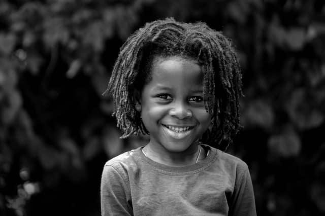 Garoto sorrindo em foto preta e branca