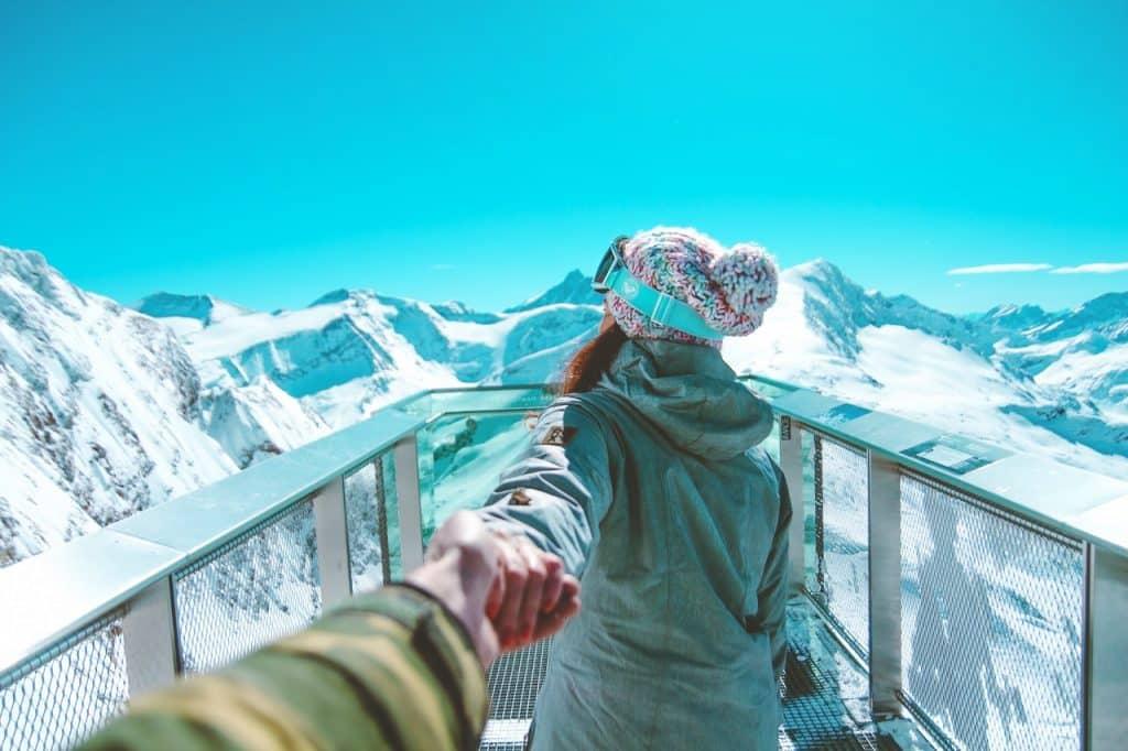 Mulher de costas usando roupas de neve, segurando mão masculina, em meio a montanhas de neve.