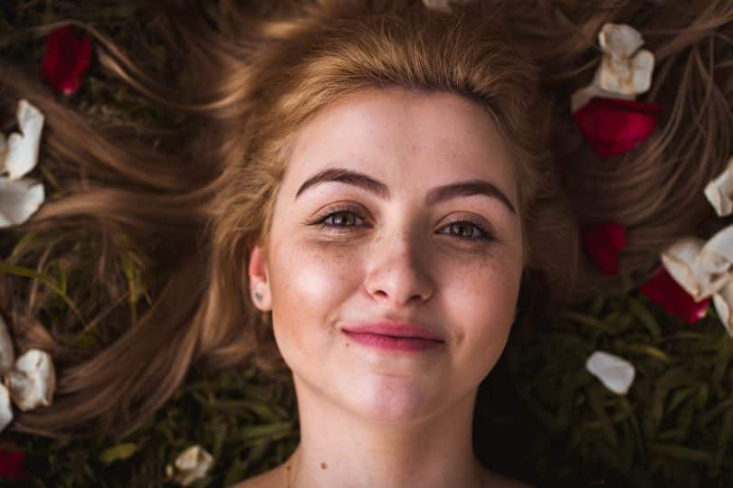 Mulher sorrindo deitada em um gramado com pétalas