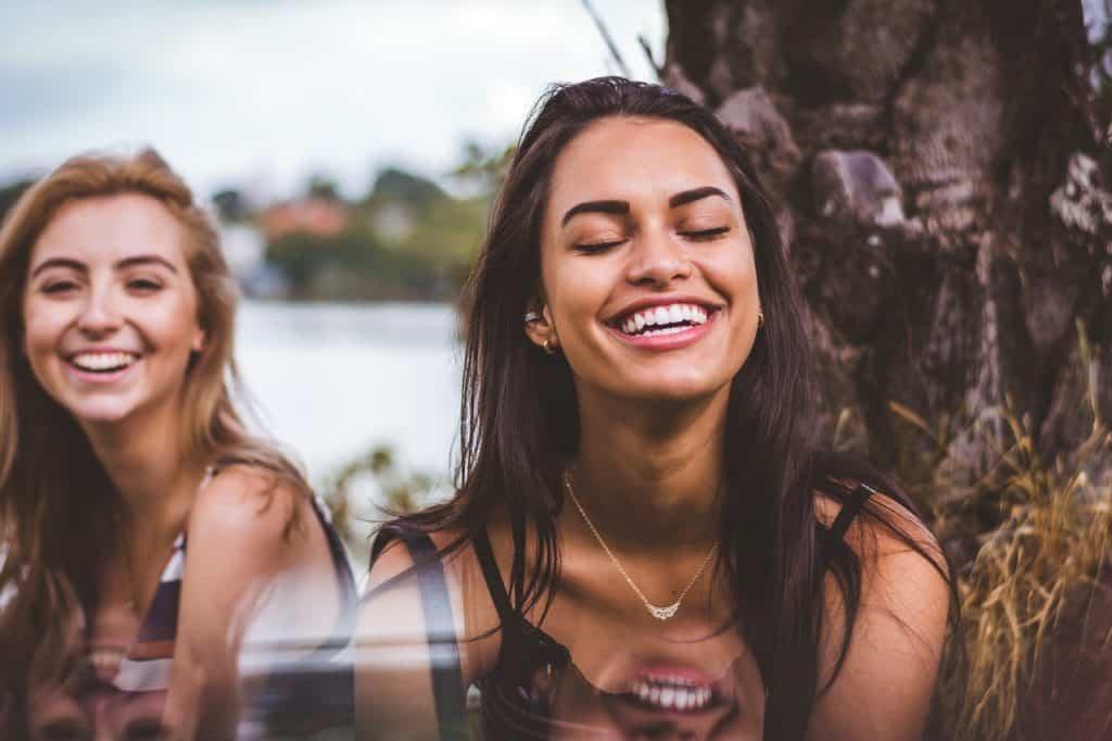 Duas mulheres sorrindo de olhos fechados ao lado de uma árvore.
