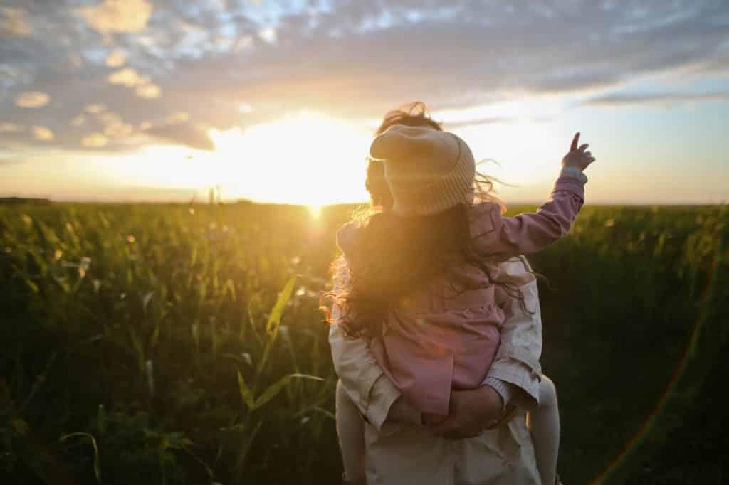 Mãe com filha no colo em meio à campo e pôr-do-sol.