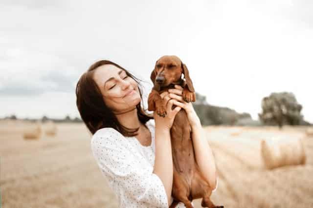 Mulher com cachorro nas mãos de olhos fechados sorrindo