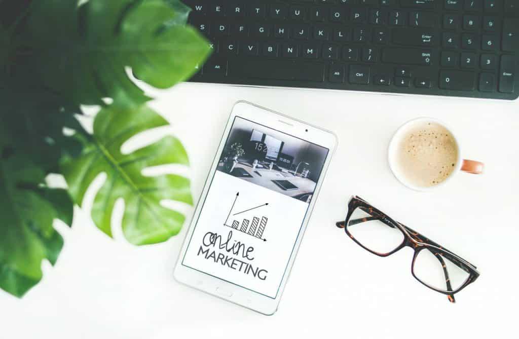 """Tablet branco escrito """"online marketing"""" ao lado de óculos marrom, xícara de café, teclado preto e planta."""