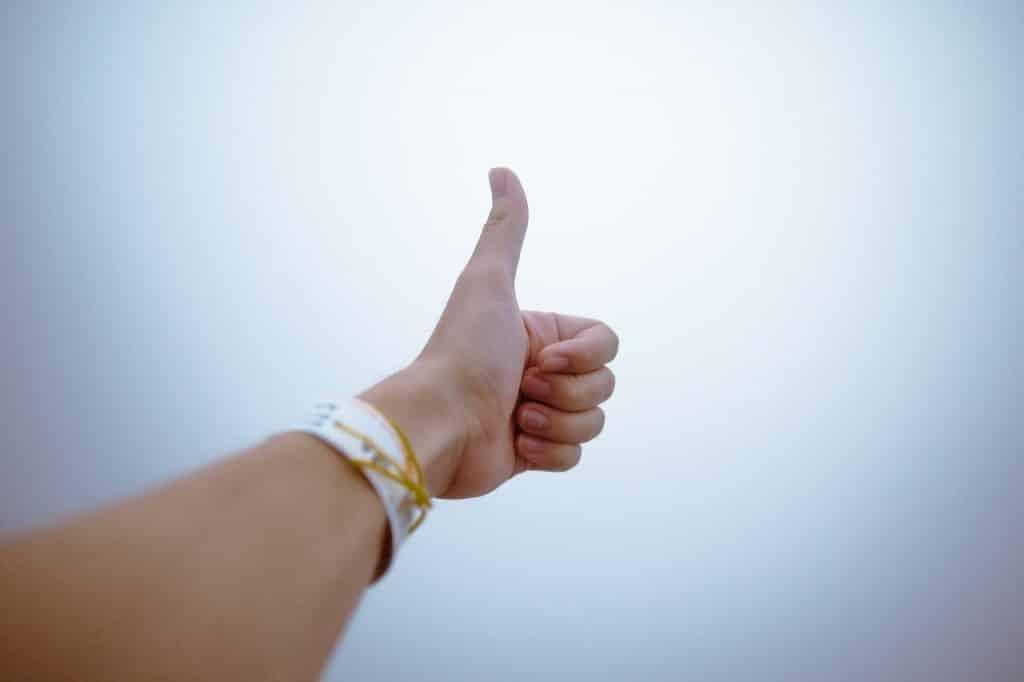 Mão de uma pessoa com seu polegar apontando para cima.