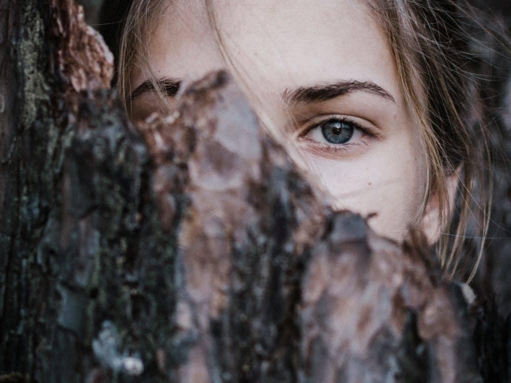 Close dos olhos de uma menina. Ela está atrás de um tronco de árvore.
