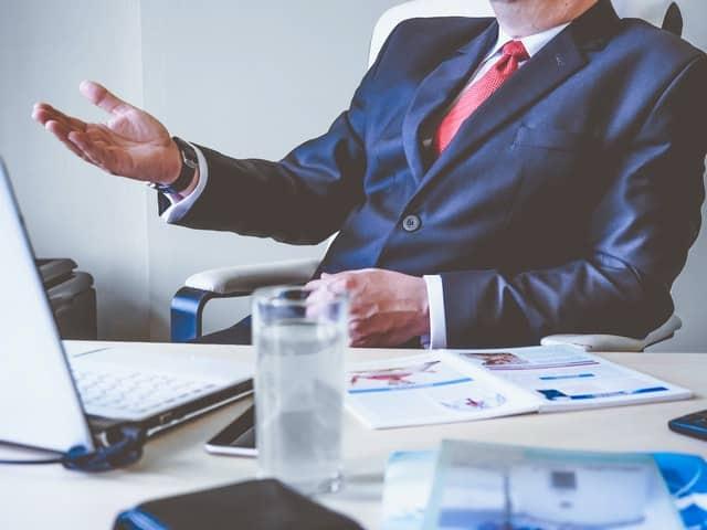 Homem sentado em mesa de trabalho usando terno e gravata com notebook e papeis na mesa