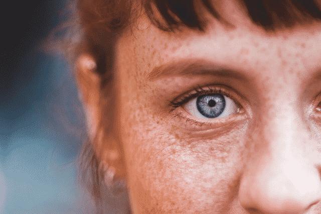 Rosto de mulher visto de perto com olho violeta