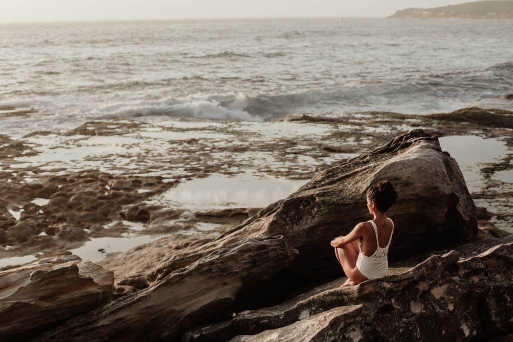 Mulher branca sentada numa rocha observando o mar