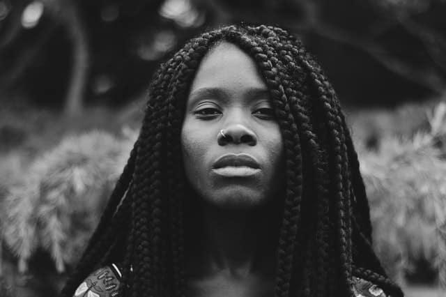 Retrato de uma mulher de cabelos trançados e expressão séria.