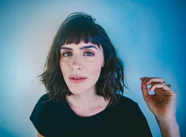 Mulher de cabelo curto e franja olhando para foto em fundo azul