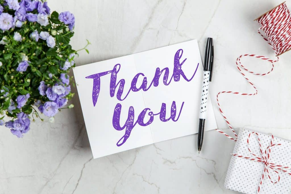 """Bilhete com os escritos """"Thank You"""" (obrigado), ao lado de flores e uma caneta."""