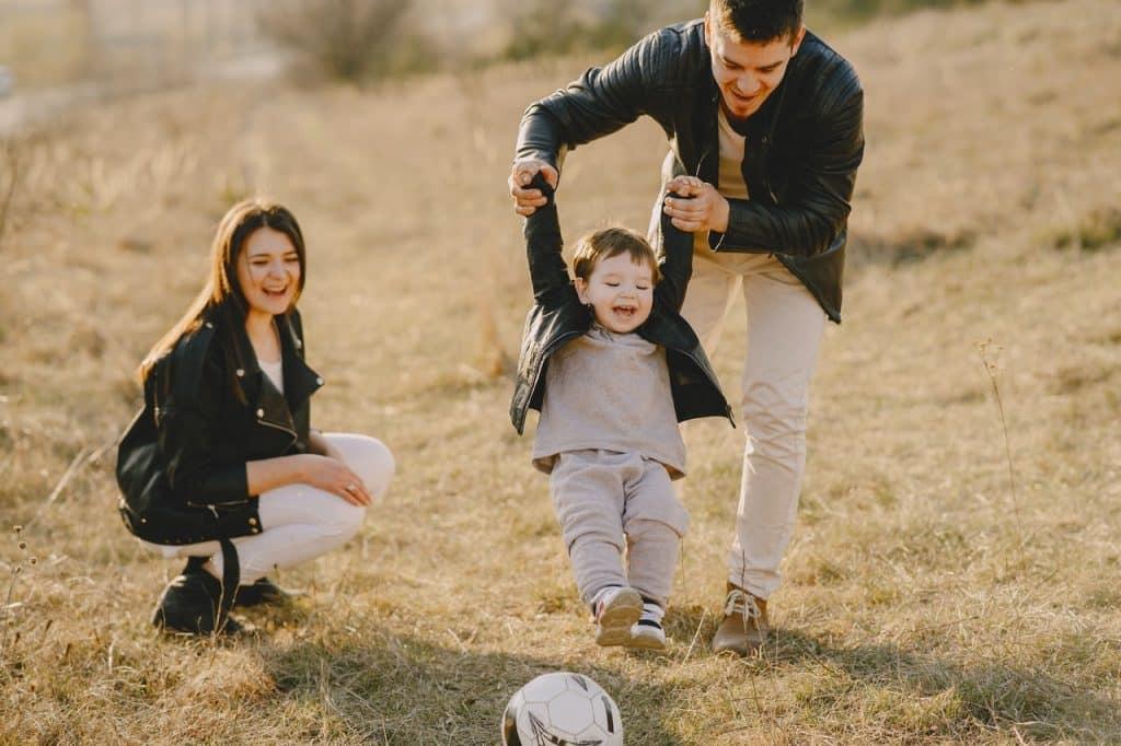 Pai, mãe e filho pequeno brincando de bola em um parque.
