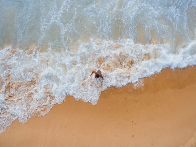 Homem saindo do mar visto de alto