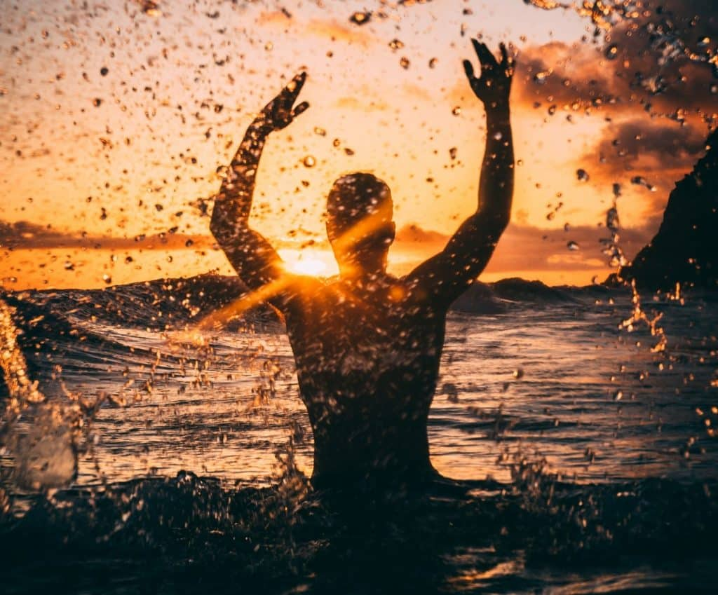 Homem no mar jogando água para o alto com pôr-do-sol ao fundo