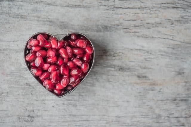 Forma de coração com grãos de romã vista de perto