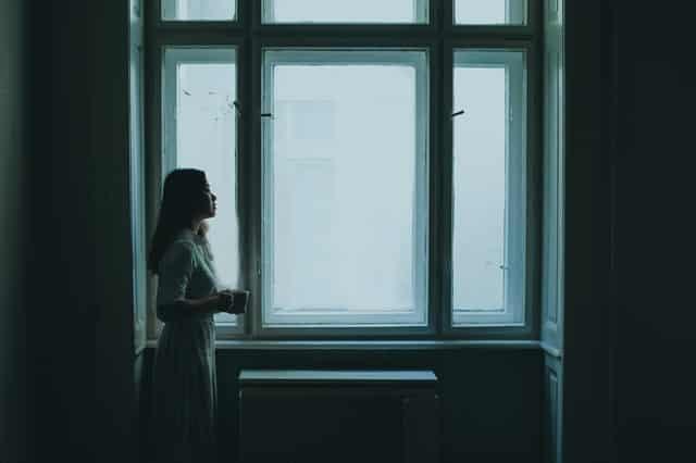 Mulher de perfil em pé com janela ao fundo em ambiente escuro