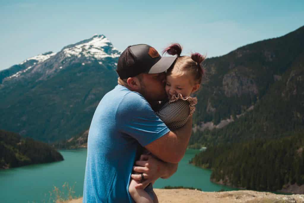 Pai abraçando e beijando a bochecha de sua filha pequena.
