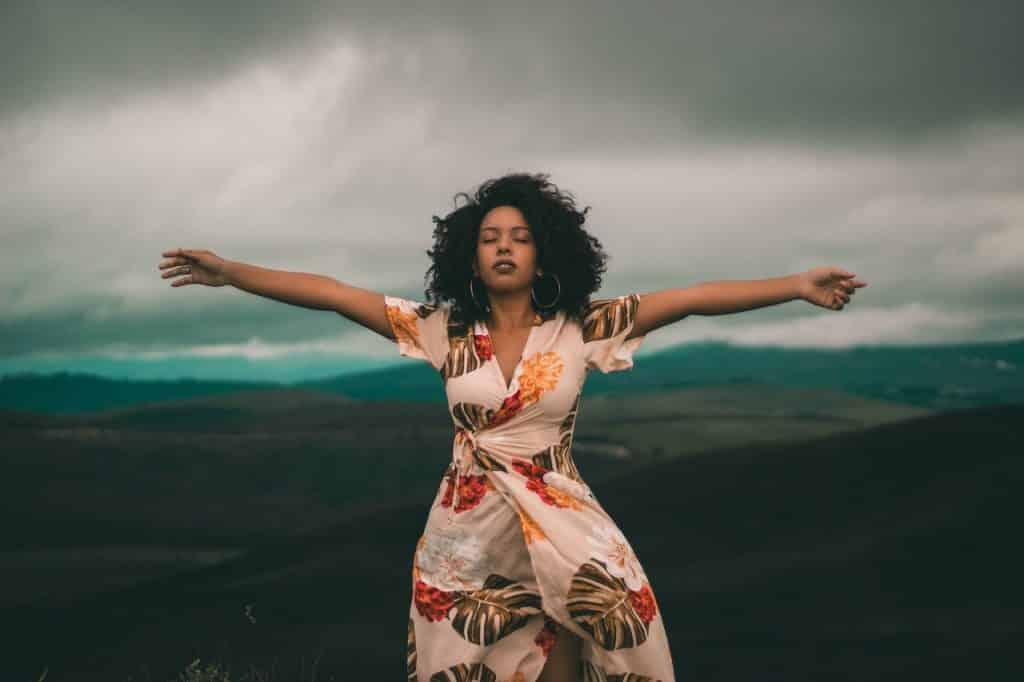 Mulher negra com braços abertos vestindo vestido estampado meio à colinas