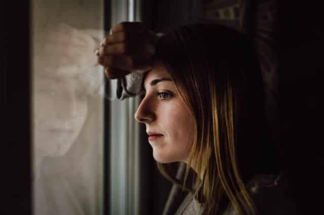Mulher apoiada na janela com olhar distante e expressão séria