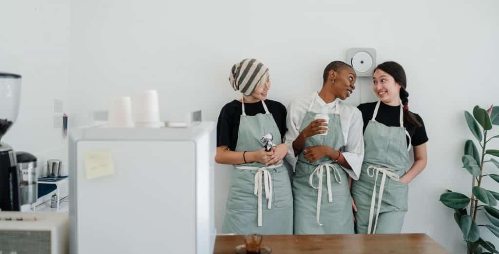 Três mulheres conversando lado a lado, usando aventais de culinária.