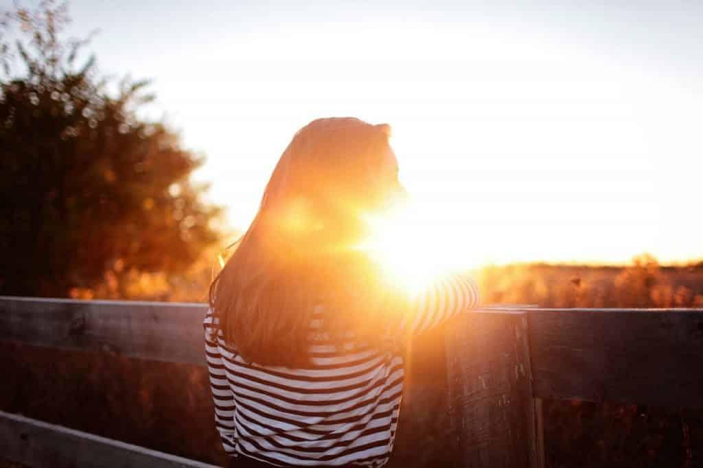 Silhueta de uma mulher de costas apoiada sobre uma cerca de madeira, ao pôr do sol.