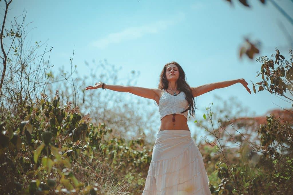 Mulher branca meditando com braços abertos ao ar livre.