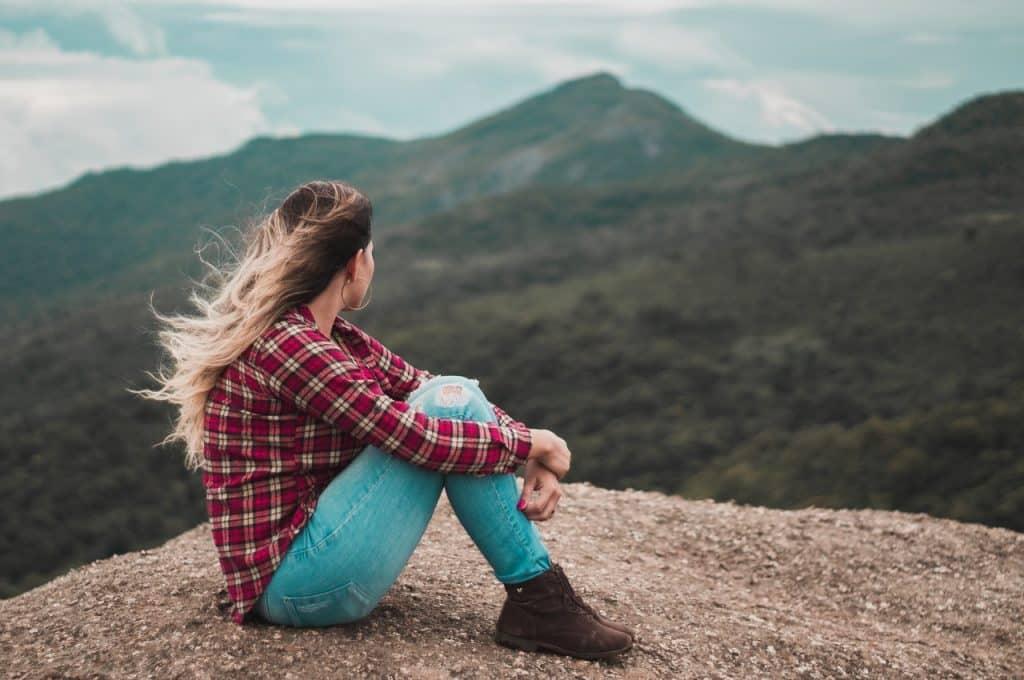 Mulher sentada em uma pedra olhando a vista à sua frente.