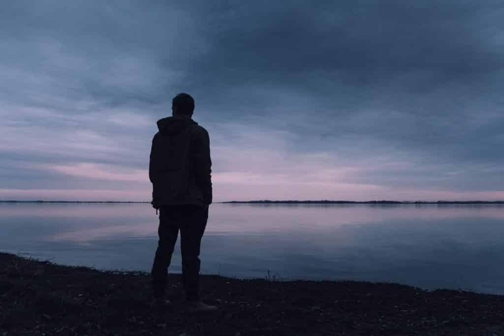 Silhueta de um homem parado em frente  a um rio, ao anoitecer.