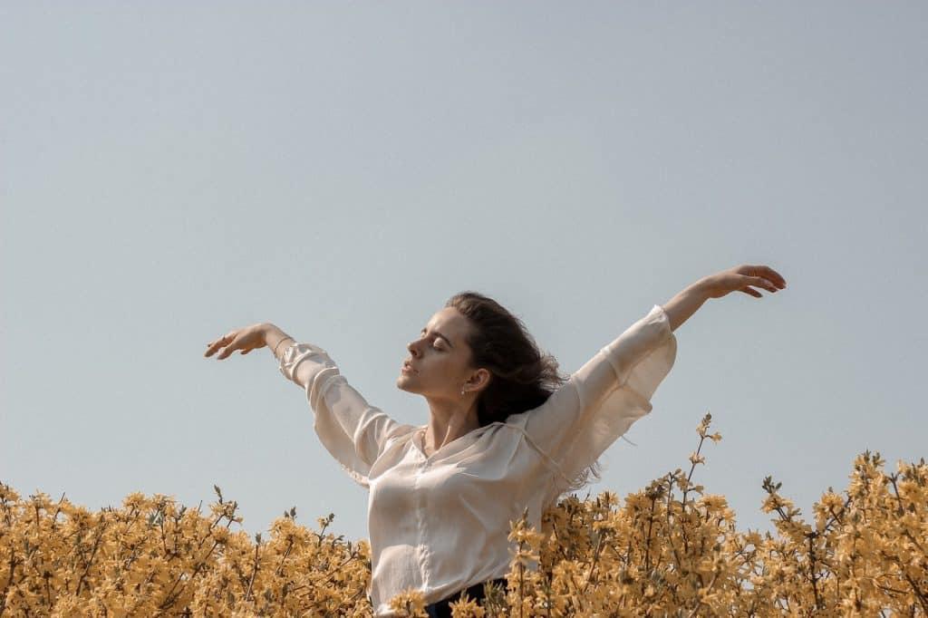 Mulher em um campo de flores, durante o dia, com as mãos para cima e os cabelos ao vento
