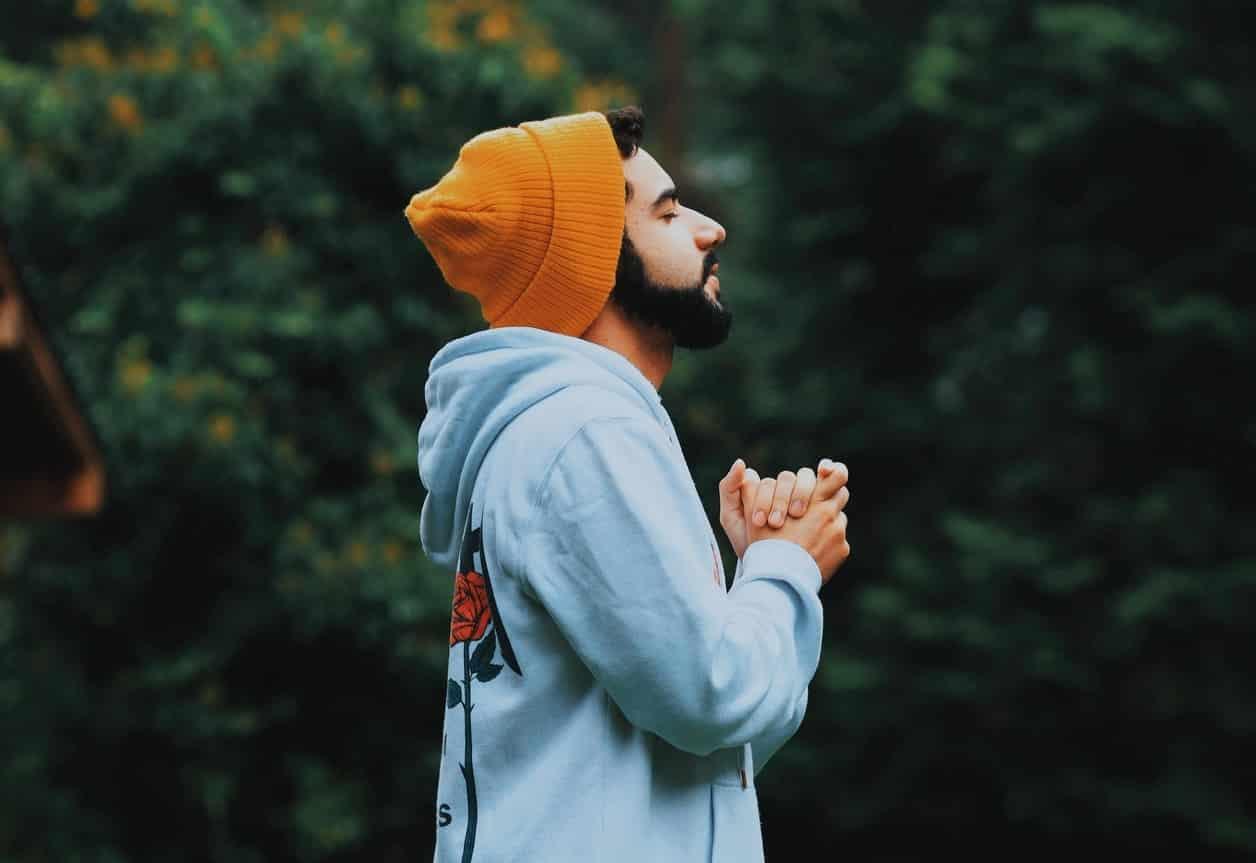 Homem em pé com mãos unidas em frente ao corpo e olhos fechados orando